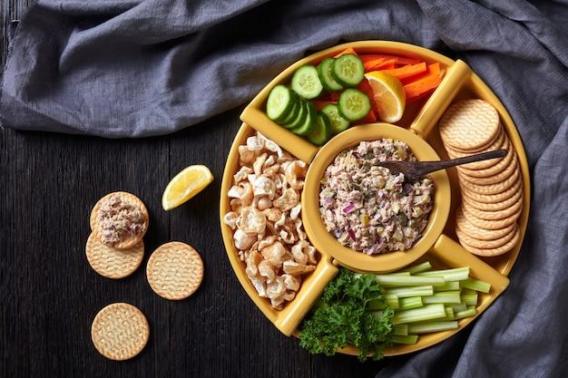 マグロのケッパーのピクルススプレッドセットにんじんとセロリのスティック、スライスした新鮮なキュウリ、クラッカー、ポークの皮を暗い木製のテーブルのボウルに入れて、フィリピン料理、フラットレイ、空きスペース