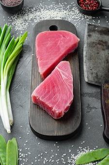 참치 필레 생 유기농 스테이크, 재료 세트, 나무 커팅 보드, 오래된 정육점 칼, 회색 돌 배경