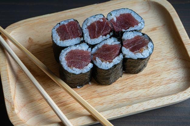 マグロの巻き寿司は木の板の上で転がります