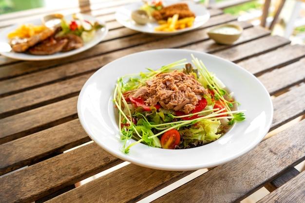 夏のカフェのテーブルの上の皿にマグロのサラダ