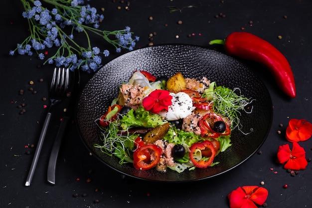 Салат из тунца в сочетании с жареным картофелем, болгарским перцем, оливками, яйцом-пашот, на подушке с салатным миксом, и заправкой на основе двух горчиц, на темной поверхности