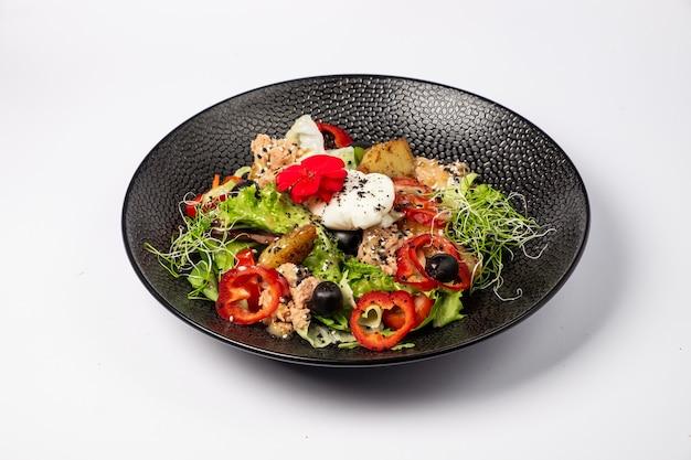 Салат из тунца в сочетании с жареным картофелем, болгарским перцем, оливками, яйцом пашот, на подушке с салатным миксом, и заправкой на основе двух горчиц, на белой поверхности