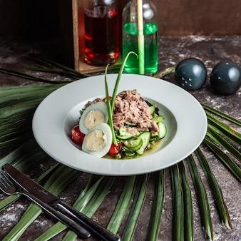 Салат из тунца в тарелке с яйцами