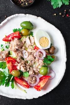 Салат из тунца овощи морепродукты помидоры оливки консервированный тунец тарелка на столе здоровое питание