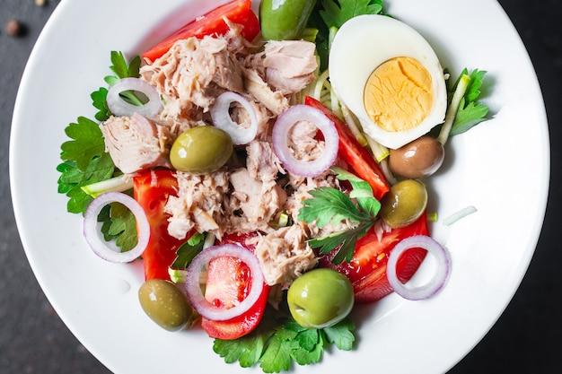 Салат из тунца овощи помидор лук зелень оливки другие консервы из тунца морепродукты на столе