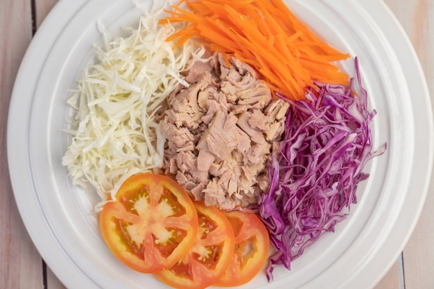 Tuna salad with carrots, tomatoes, cabbage on a white plate on a wooden floor.