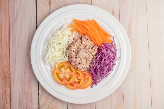 Insalata di tonno con carote, pomodori, cavolo su un piatto bianco su un pavimento di legno.