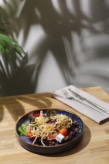 죽은 태아와 토마토가 나무 테이블에 근접한 참치 샐러드.