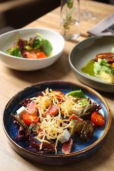Салат из тунца с фетой и помидорами. стол с едой. концепция ужина.