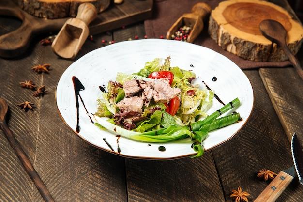 Салат из тунца со свежей зеленью салата на деревянном столе