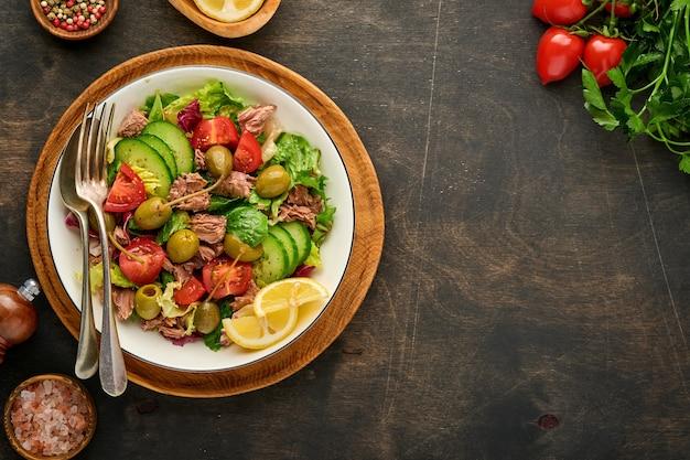 Салат из тунца со свежими овощами, оливками, каперсами и лимоном подается в миске
