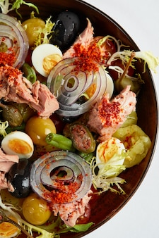 Tuna salad with fresh vegetables on a white napkin, classic nicoise in the author's presentation, canned tuna with masilnas, onions and eggs, top view.