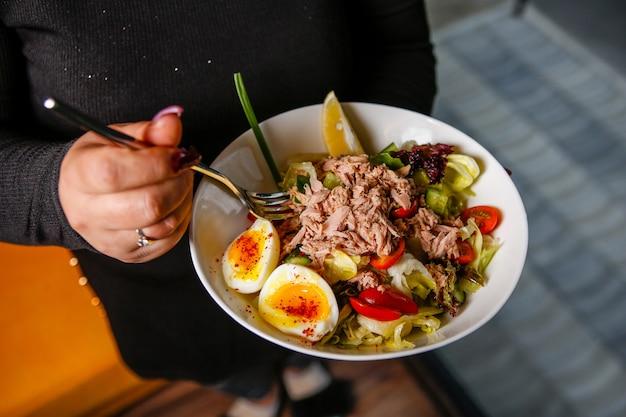 Салат из тунца с листьями салата, яйцом, огурцом и помидором