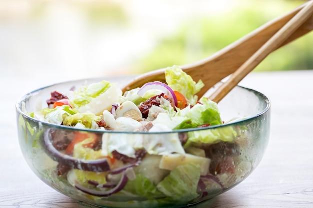Салат из тунца с листьями салата, яйцом и вялеными помидорами. вкусный рыбный салат