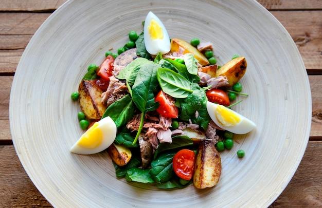 Салат из тунца с салатом, яйцом и помидорами на деревянной тарелке