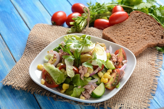 Tuna salad with lettuce, eggs and tomatoes, cucumber, corn and red onion.