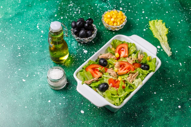 Tuna salad with lettuce,olives,corn,tomatoes,top view