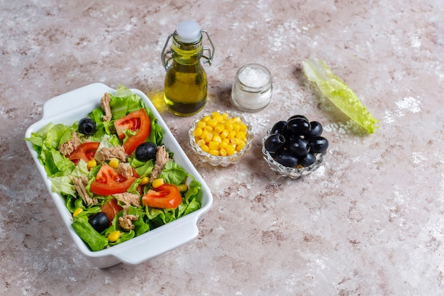 Tuna salad with lettuce, olives, corn, tomatoes, top view
