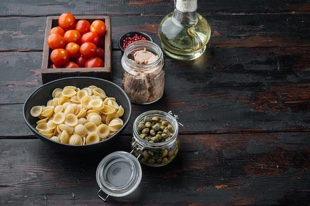 어두운 나무 테이블에 파스타와 야채 재료와 참치 샐러드
