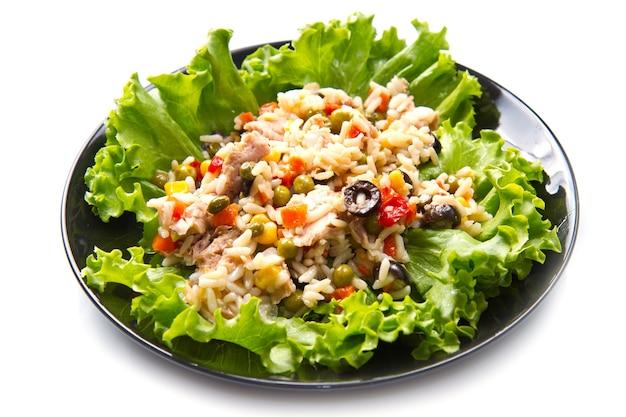 검은 접시에 쌀과 야채와 참치 샐러드