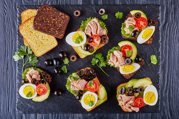 Tuna sandwiches with avocado slices, lettuce, tomatoes, black olives and hard boiled egg on a rye and corn toasted bread on a black slate tray on a wooden table