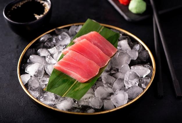 Сашими из тунца на льду в черной тарелке