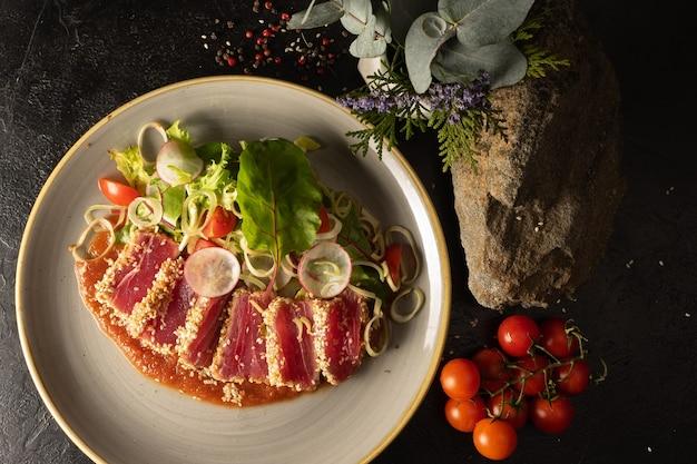 체리 토마토, 무, 양파, 양상추, 아지 카 토마토 소스의 야채 샐러드를 곁들인 참치 슬라이스