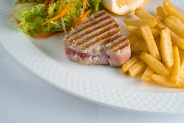 당근, 파스닙, 양상추, 레몬을 흰색 바탕에 흰색 접시에 얹은 감자튀김 샐러드와 함께 구운 참치 스테이크.