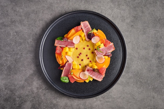 Tuna steak salad, mango sauce, herbs and spices on a dark plate, top view, copy space, food decorating concept