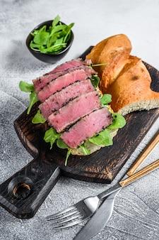 Сэндвич со стейком из тунца в багете с рукколой. белый фон. вид сверху.