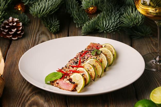 マグロのライムステーキ。白ワインのガラスとクリスマスの装飾にゴマでスライスしたマグロのステーキ