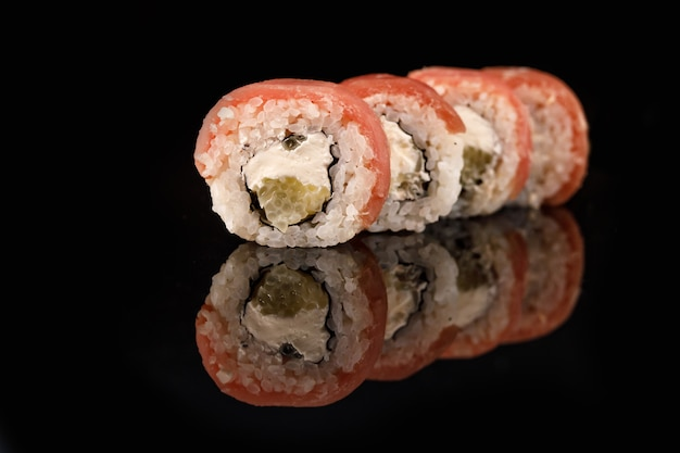 Tuna sushi roll on a black surface with reflection.