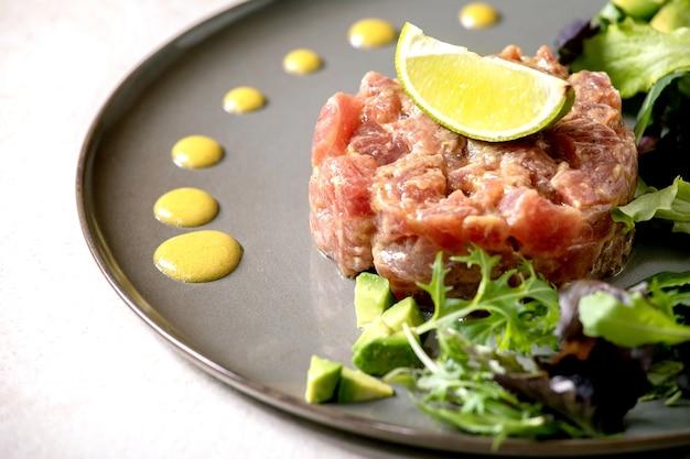 セラミックプレートにグリーンサラダ、ライム、アボカド、マスタードソースを添えたマグロのタルタル。高級ダイニング、レストランの前菜