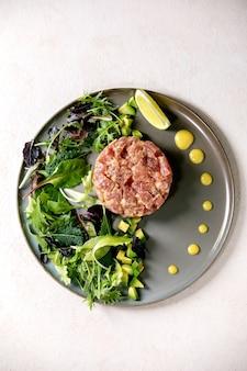 セラミックプレートにグリーンサラダ、ライム、アボカド、マスタードソースを添えたマグロのタルタル。フラットレイ、コピースペース。高級ダイニング、レストランの前菜