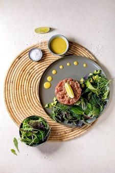 マグロのタルタルとグリーンサラダ、ライム、アボカド、マスタードソースを白いテクスチャーの背景にストローナプキンのセラミックプレートで提供しています。フラットレイ、コピースペース。