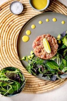 マグロのタルタルとグリーンサラダ、ライム、アボカド、マスタードソースを白いテクスチャーテーブルの上のストローナプキンのセラミックプレートに添えます。フラットレイ、コピースペース。高級レストラン、レストランの前菜
