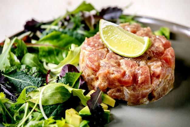 マグロのタルタルステーキ、グリーンサラダ、ライム、アボカド、マスタードソースを白いテクスチャーテーブルのセラミックプレートに添えて。高級レストラン、レストランの前菜