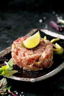 マグロのタルタルとグリーンサラダ、ライム、アボカド、マスタードソースを黒大理石のテーブルの上に和風の黒セラミックプレートで添えます。レストランの前菜。閉じる