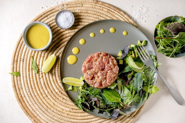 Tuna tartare with green salad, lime, avocado and mustard sauce serving on ceramic plate on straw napkin over white texture background. flat lay, copy space.