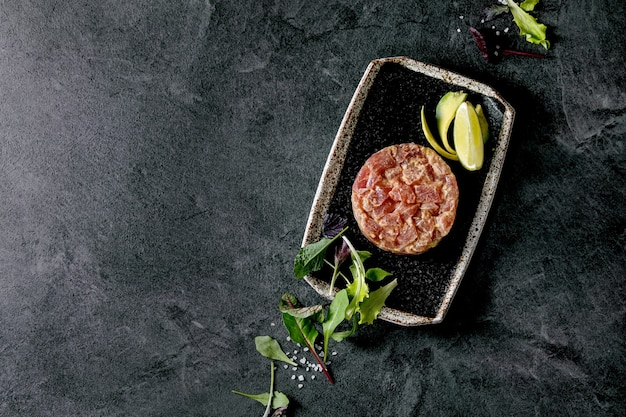 Tuna tartare with green salad, lime, avocado and mustard sauce serving on japanese style black ceramic plate over black marble background. flat lay, copy space. restaurant appetizer