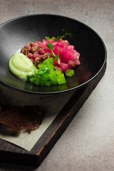 Тартар из тунца с маринованными огурцами и соусом на черной тарелке