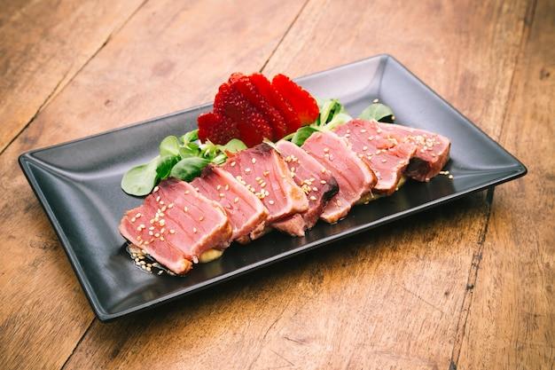 Блюдо татаки из тунца с клубникой, каноном и кунжутным соусом на деревенском деревянном столе