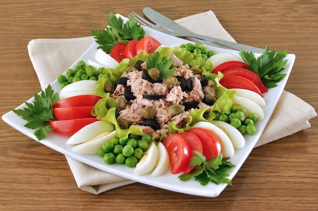 Тунец с оливками и каперсами в окружении нарезанных кубиками овощей