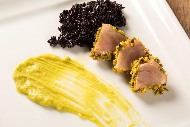 Тунец с фисташковой корочкой, черным рисом и пюре из авокадо