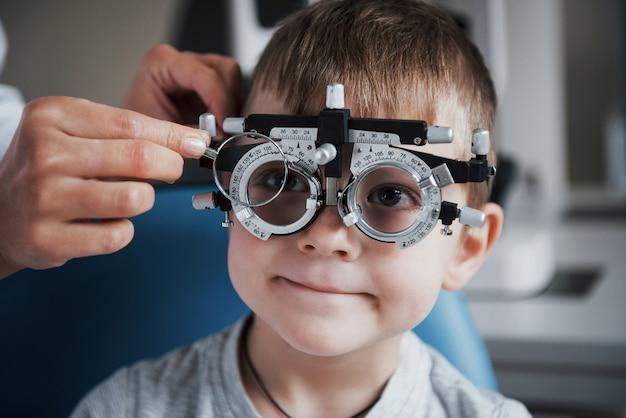 Настройка инструмента. маленький мальчик с фороптером проверяет свои глаза в кабинете врача.