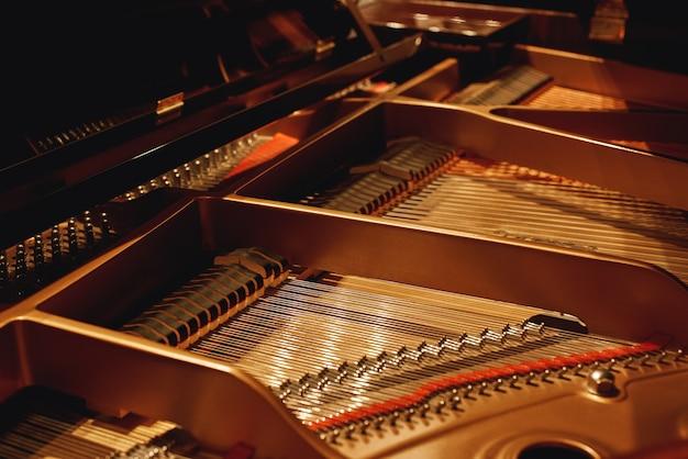 Настройка вашего фортепиано. крупным планом - молотки, струны и булавки внутри фортепиано. музыкальные инструменты. механизм пианино