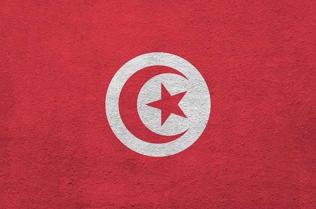 Tunisia flag depicted in bright paint colors on old relief plastering wall.