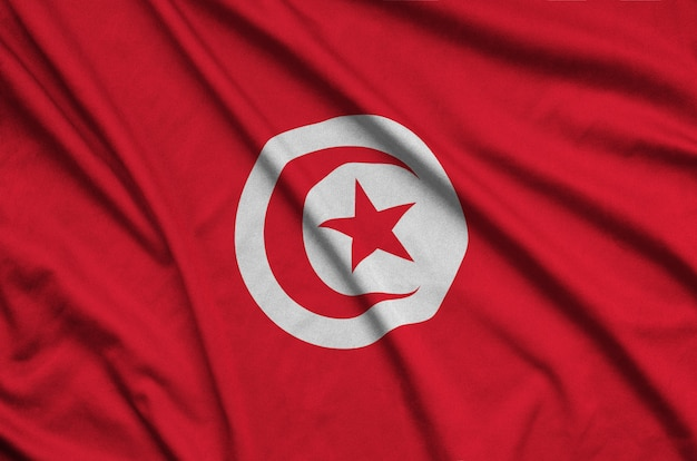 Tunisia flag  is depicted on a sports cloth fabric with many folds.