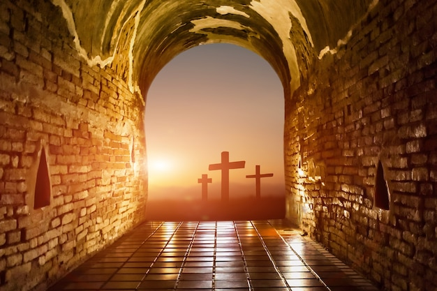 일출 배경에서 예수 그리스도의 십자가와 부활을 향한 터널. 기독교 종교 개념입니다.