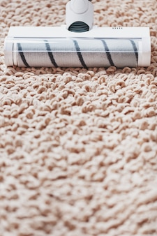 The turbo brush of a cordless vacuum cleaner cleans the carpet in the house in closeup